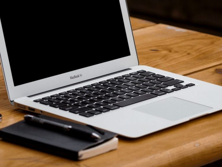Picture of a MacBook Air on a desk with a business notebook and coffee alongside